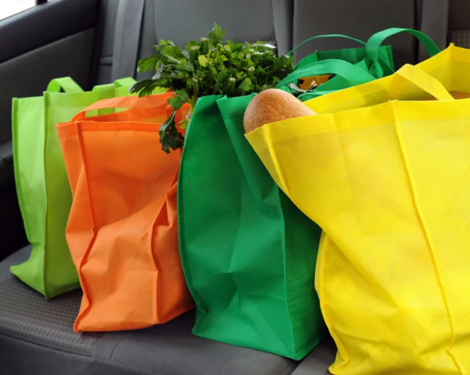 Cloth bags filled with groceries.